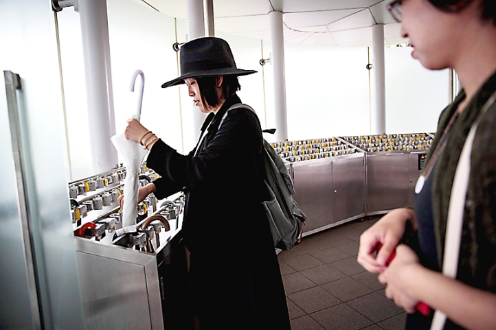 In this picture taken on September 4, 2017, a Japanese woman takes her umbrella at an umbrella lock-up in Tokyo's National Art Center. Heated toilets that spray users clean, train seats that revolve so passengers can admire the scenery and a convenience store on every corner: welcome to Japan, where hospitality and customer service form part of the country's DNA. / AFP PHOTO / Behrouz MEHRI / TO GO WITH Japan-social-Lifestyle, FOCUS by Anne BEADE